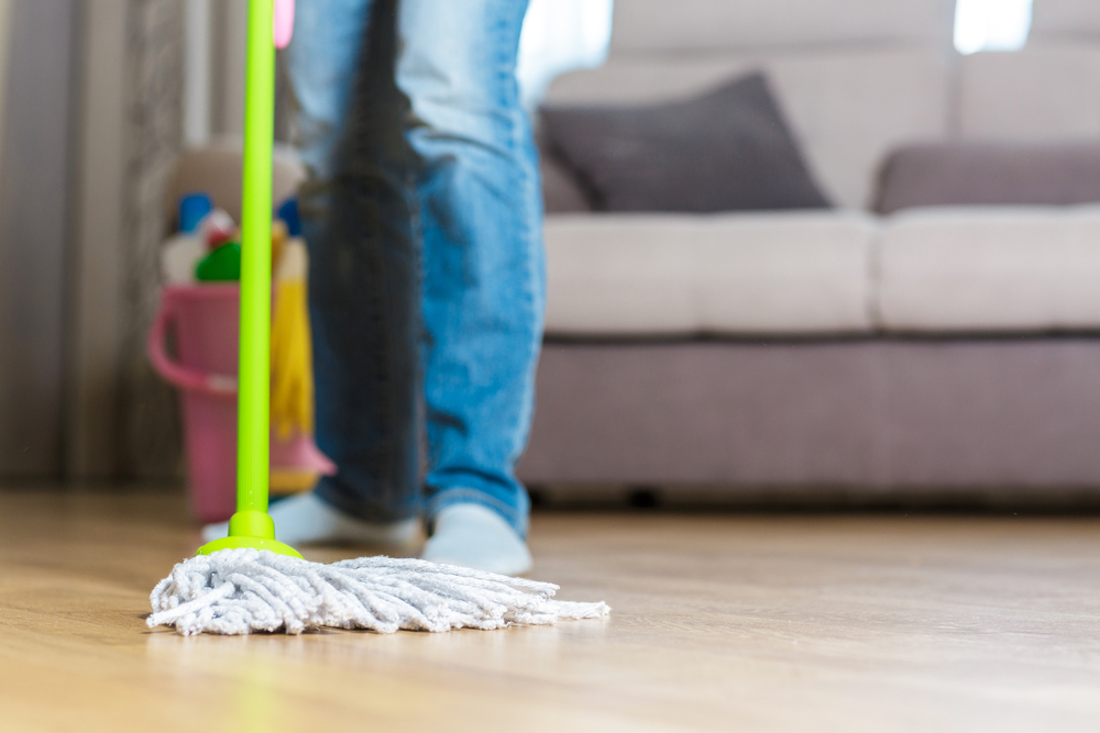 Person mopping a hardwood floor.