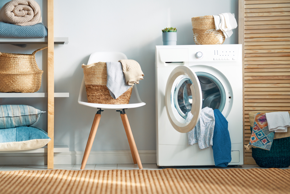 Modern laundry room with clothes hanging out of washing machine